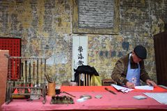 FOSHAN, CINA - CIRCA GENNAIO 2019: Un uomo anziano che scrive benedicendo i distici fotografie stock