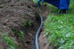 Foso excavado de la tierra para el tendido de tuberías de la comunicación y del cableado eléctrico bajo tierra para proporcionar  imagen de archivo