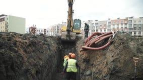 Fossa di scavatura dell'escavatore lento con due lavoratori in cappelli arancio in  stock footage