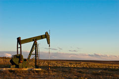 Fossil fuel statue. Dormant oil or natural gas pump alone on vast prairie with storm clouds in the distance Stock Images
