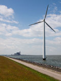 Fossil versus wind. A wind turbine with a fossil fueled power plant in the backdrop Stock Photos