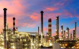 Fossila bränslenraffinaderi på skymning - petrokemisk fabrik arkivfoto