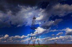 Fossila bränslenrigg som profileras på illavarslande stormig himmel royaltyfria bilder