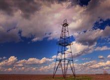 Fossila bränslenrigg som profileras på illavarslande stormig himmel royaltyfri fotografi