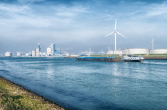 Fossile and new energy. Wind turbines and storage silos for petrol in the rotterdam harbor area Royalty Free Stock Photo