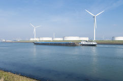 Fossile and new energy. Wind turbines and storage silos for petrol in the rotterdam harbor area Royalty Free Stock Photos