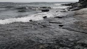 Black and white Lake Champlain waves over chazy limestone stock photography
