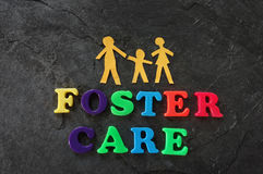 Foster care family. Paper family with Foster Care letters Royalty Free Stock Photo