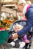 Fostra att göra ren handen från hennes lilla daugther i barnvagnen fotografering för bildbyråer