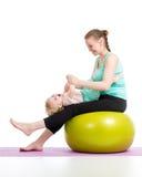 Fostra att göra som är gymnastiskt med, behandla som ett barn på konditionboll Royaltyfria Bilder