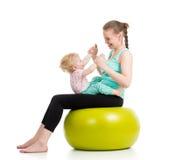 Fostra att göra som är gymnastiskt med, behandla som ett barn på konditionboll Arkivfoton