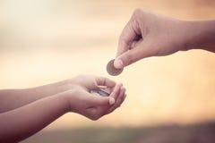 Fostra att ge myntet till barnet som sparande pengarbegrepp Royaltyfria Foton