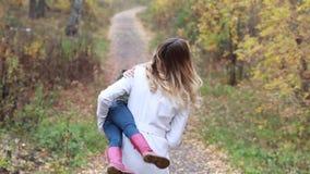 Fostra att ge ritt för dotter på ryggen i höstskogsmark arkivfilmer