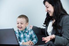 Fostra att ha en stor tid med hennes pojke, medan se datoren Fotografering för Bildbyråer