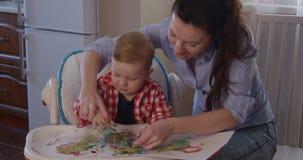 Fostra att ha gyckel med hennes Little Boy och målarfärg med fingrar arkivfilmer