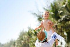 Fostra att ha gyckel på stranden med hennes lilla son Royaltyfria Foton