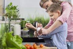 Fostra att hjälpa sonen i hopfällbara muffar, medan tvätta händer i kök Arkivfoton