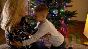 Fostra att killa hennes gulliga son under julträd arkivfilmer