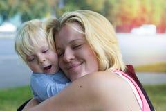 Fostra att krama hennes son som upp skruvas henne ögon i nöje Royaltyfri Bild