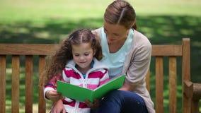 Fostra att läsa en berättelse till hennes dotter på en bänk Fotografering för Bildbyråer