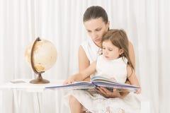 Fostra att läsa en bok till hennes lilla dotter hemma fotografering för bildbyråer