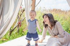 Fostra att le att skratta och att spela med hennes barn Arkivbild