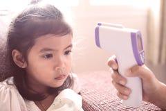 Fostra att mäta temperatur hennes sjuka asiatiska flicka för det lilla barnet Arkivfoto