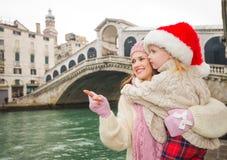 Fostra att peka på något till barnet som bär Santa Hat, Venedig Royaltyfria Foton