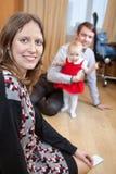 Fostra att se kameran, medan fadern som spelar med, behandla som ett barn flickan i inhemskt rum Royaltyfri Foto