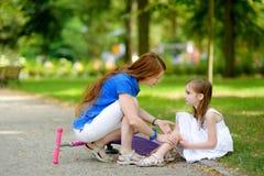 Fostra att trösta hennes dotter, efter hon har avverkat, medan rida hennes sparkcykel Arkivfoton