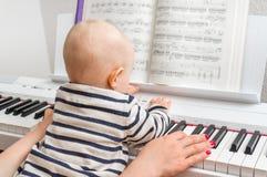 Fostra att undervisa hennes gulligt behandla som ett barn för att spela pianot royaltyfri foto