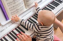 Fostra att undervisa hennes gulligt behandla som ett barn för att spela pianot royaltyfri fotografi