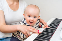 Fostra att undervisa hennes gulligt behandla som ett barn för att spela pianot arkivfoto