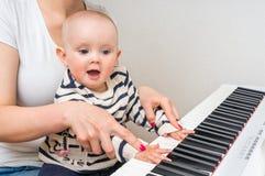 Fostra att undervisa hennes gulligt behandla som ett barn för att spela pianot arkivbilder