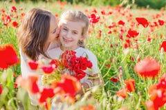 Fostra brunetten i vit med dottern tillsammans på att blomstra det röda vallmofältet Arkivbild