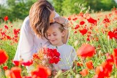 Fostra brunetten i vit med dottern tillsammans på att blomstra det röda vallmofältet Royaltyfri Bild