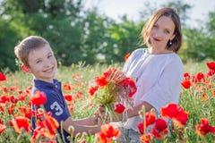 Fostra brunetten i vit med sonen tillsammans på att blomstra det röda vallmofältet Fotografering för Bildbyråer