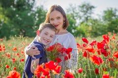 Fostra brunetten i vit med sonen tillsammans på att blomstra det röda vallmofältet Royaltyfri Foto