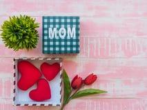 Fostra dagbegreppet för ` s röd hjärta, tulpan blommar och giftbox på p royaltyfri fotografi
