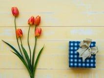 Fostra dagbegreppet för ` s tulpanblomma och giftbox på pastellfärgad yello fotografering för bildbyråer