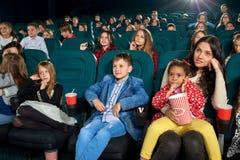 Fostra den hållande ögonen på filmen med barn i bion royaltyfri fotografi
