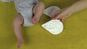 Fostra den satta foten och gömma i handflatan avtryckar som fläckar nära nyfött behandla som ett barn arkivfilmer