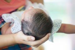 Fostra det hållande huvudet av hennes nyfött behandla som ett barn flickan i hand Royaltyfri Fotografi