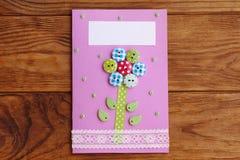 Fostra för dag- eller mammafödelsedaghälsningen för ` s kortet med blomman som isoleras på en träbakgrund Lätt handgjort kort som arkivbild