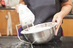 Fostra genom att använda elvispen för att blanda ingredienser av sockerkakan Royaltyfria Bilder
