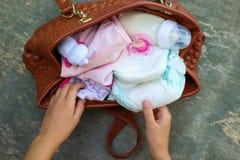 Fostra handväskan för ` s med objekt för att att bry sig för barn arkivbilder