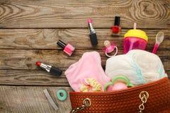 Fostra handväskan för ` s med objekt för att att bry sig för barn och skönhetsmedel arkivbilder
