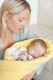 Fostra innehav som hon som sovar, behandla som ett barn, som slås in upp i en täcka Royaltyfri Bild