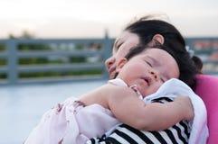 Fostra innehavet som hennes nyfött behandla som ett barn i sexig klänning, medan hon sov Baby sover på hennes moderskuldra på tak Royaltyfria Foton