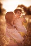 Fostra kommunikationen med dottern i ett vetefält Royaltyfri Bild